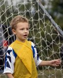 Soccer Player. Young boy soccer player standing in front of goal net Royalty Free Stock Photo