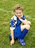 Soccer Player. Young soccer player sitting on ball on sideline waiting turn Stock Photography