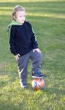 Soccer Player. Young boy with foot on top of ball surveying field royalty free stock photo