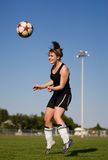 Soccer player. A female soccer player heading the soccer ball Royalty Free Stock Photography