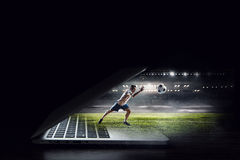 Soccer player in action. Mixed media. Soccer player jumping of laptop and kicking ball. Mixed media royalty free stock photo