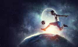 Soccer player in action. Mixed media. Soccer player running on Earth planet and kicking ball. Mixed media. Elements of this image are furnished by NASA royalty free stock photography