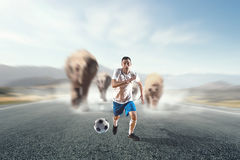 Soccer player in action. Mixed media Royalty Free Stock Photography