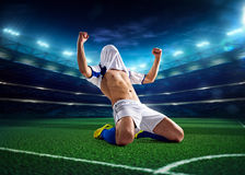 Soccer player in action. On night stadium background Royalty Free Stock Photography