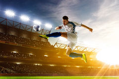 Soccer player in action. On night stadium background Stock Images