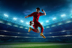 Soccer player in action. On night stadium background Stock Photos
