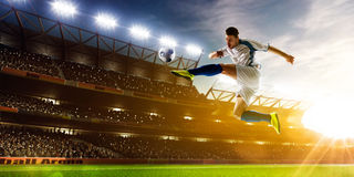 Soccer player in action. On night stadium background panorama