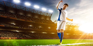 Soccer player in action. On night stadium background panorama Royalty Free Stock Photo