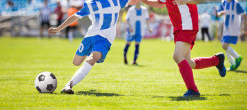 Soccer Player Action On Stadium. Youth Football Tournament Game. Young Boys Running and Kicking Soccer Ball on Green Soccer Pitch.  Stock Photos