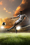 Soccer player in action on sunset stadium background Stock Photo