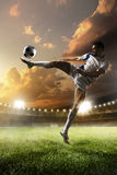 Soccer player in action on sunset stadium background Stock Photography