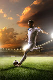 Soccer player in action on sunset stadium background Royalty Free Stock Photography