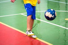 Soccer player in action. Teenager playing soccer on court Stock Image