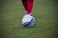 Soccer player approaches soccer ball. Royalty Free Stock Image