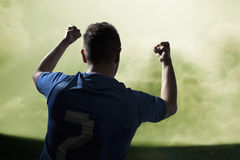Soccer player with arms raised cheering, stadium with green sky Stock Images