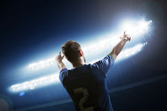 Soccer player with arms raised cheering, stadium at night time stock photography