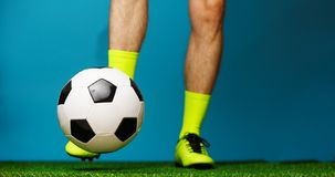 Soccer player with ball on the green grass. Soccer player with ball on the green grass and blue background royalty free stock photos