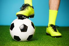 Soccer player with ball on the green grass. Soccer player with ball on the green grass and blue background stock photos