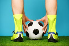 Soccer player with ball on the green grass. Soccer player with ball on the green grass and blue background royalty free stock photo