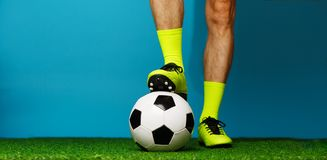 Soccer player with ball on the green grass. Soccer player with ball on the green grass and blue background royalty free stock photography
