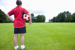 Soccer player with ball looking down field Stock Photography