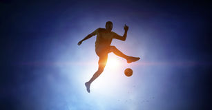 Soccer player with ball outdoors. Silhouette of soccer player jumping and kicking ball Royalty Free Stock Image