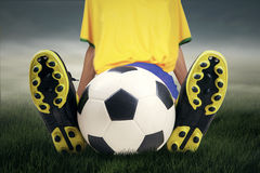 Soccer player with ball resting on grass Royalty Free Stock Images