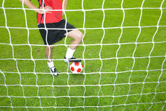 Soccer player with ball standing at goal net Stock Photo