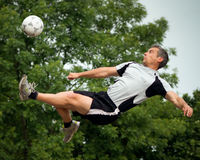 Soccer player in a bicycle kick. Soccer player doing a bicycle kick Royalty Free Stock Image