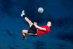 Soccer player in a bicycle kick. Soccer player doing a bicycle kick Royalty Free Stock Images