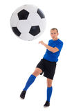 Soccer player in blue kicking ball isolated on white background Stock Photo