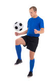 Soccer player in blue uniform playing with ball isolated on whit Royalty Free Stock Image