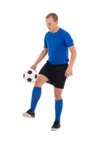Soccer player in blue uniform playing with ball on white backgro Royalty Free Stock Images