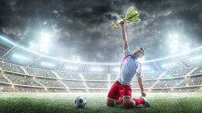 Soccer player celebrates winning the open stadium. Soccer player holds a trophy one hand . Medal on the neck. The winner stock images