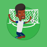 Soccer player celebrating scoring goal. African-american football player celebrating scoring goal. Football player kneeling on the background of football gate Stock Photography