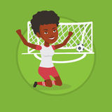 Soccer player celebrating scoring goal. African soccer player celebrating scoring goal. Football player kneeling with raised arms on the background of gate with Stock Images