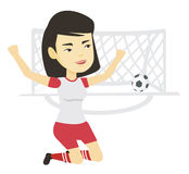 Soccer player celebrating scoring goal. Asian soccer player celebrating scoring goal. Football player kneeling with raised arms on the background of football Stock Image