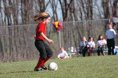 Soccer Player Chasing Ball 2. Girl soccer player chasing ball during game play Royalty Free Stock Photo