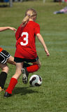 Soccer Player Chasing Ball. Girl soccer player chasing ball during game play Royalty Free Stock Photography