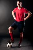 Soccer player in dark. Soccer player is standing with ball on dark background Royalty Free Stock Images