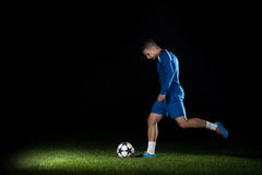Soccer Player Doing Kick With Ball. On Football Stadium Field  On Black Background Royalty Free Stock Photography