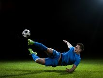 Soccer player. Doing kick with ball on football stadium  field  isolated on black background Stock Photos