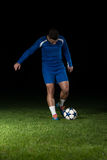 Soccer Player Doing Kick With Ball. On Football Stadium Field Isolated On Black Background Stock Photos