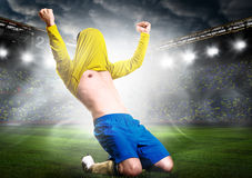 Soccer player. Soccer or football player is celebrating goal on stadium with his jersey on head Royalty Free Stock Images