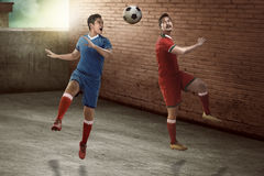 Soccer player header on the alley. Image of soccer player header on the alley. Street soccer concept Stock Image