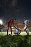 Soccer player helps onother one on sunset stadium background panorama Royalty Free Stock Image