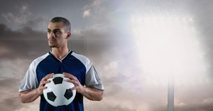 Soccer player holding ball against floodlight Royalty Free Stock Photos
