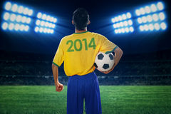 Soccer player holding ball at field Stock Images