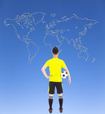 Soccer player holding a soccer and looking global map Royalty Free Stock Photography