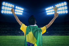 Soccer player holding trophy at field Stock Photo